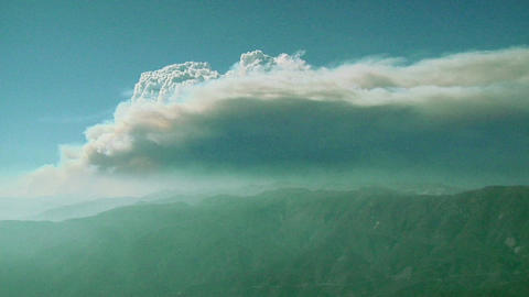 Smoke billows from a mountain wildfire Stock Video Footage
