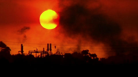 Smoke moves across the sky in an industrial area during... Stock Video Footage