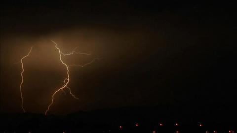 Lightening strikes illuminate a dark sky Footage
