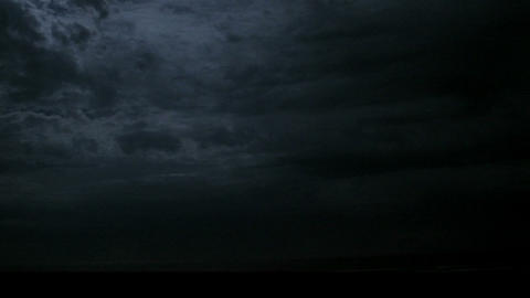 Lightning flashes under fast-moving storm clouds Stock Video Footage