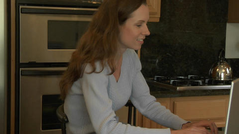 A woman sits at a kitchen counter and types on a laptop... Stock Video Footage