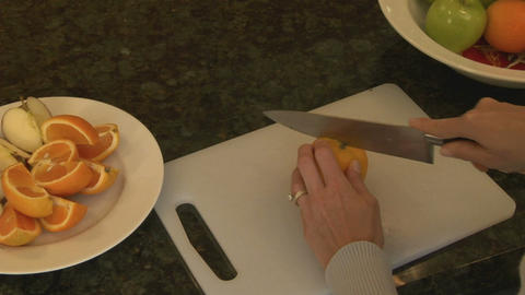 A woman slices oranges on a cutting board Stock Video Footage