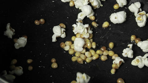 Kernels of popcorns explode in a pan of oil Footage