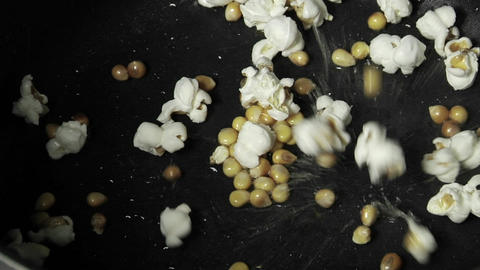Kernels of popcorns explode in a pan of oil Stock Video Footage