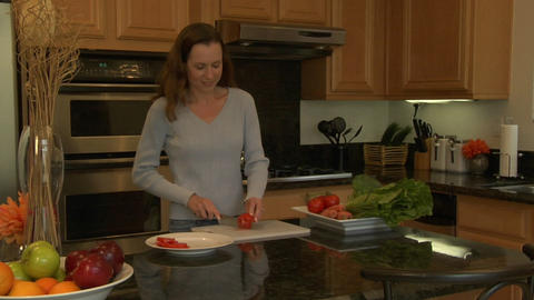 A woman slices tomatoes on a cutting board Stock Video Footage
