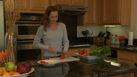 A woman slices tomatoes on a cutting board Footage