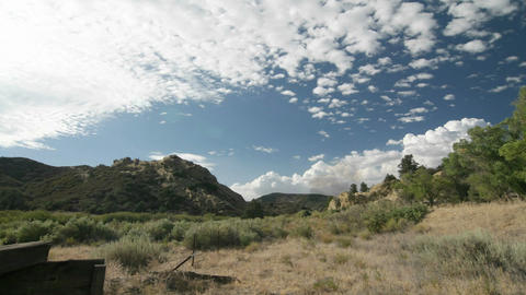 Clouds move across the sky above a California mountain scene Stock Video Footage