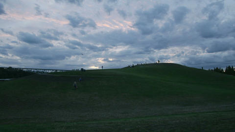 Clouds and people move across the sky behind a landfill Stock Video Footage