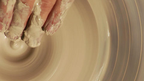 A potter works on a potter wheel from above Stock Video Footage