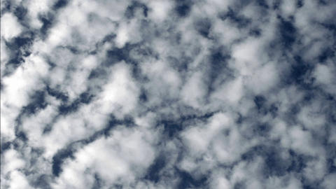 White clouds drift across a blue sky Footage