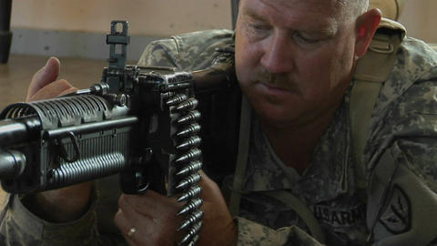 A man prepares to fire an automatic weapon Stock Video Footage
