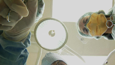 Surgeons look down on a patient and use instruments Stock Video Footage
