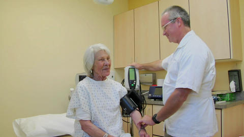 A medical professional takes the blood pressure of an... Stock Video Footage