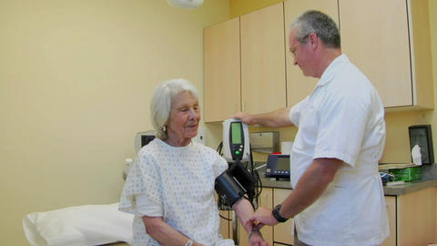 A medical professional takes the blood pressure of an elderly patient Footage