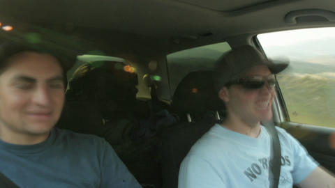 A passenger and a driver in a car smoke and eat Stock Video Footage