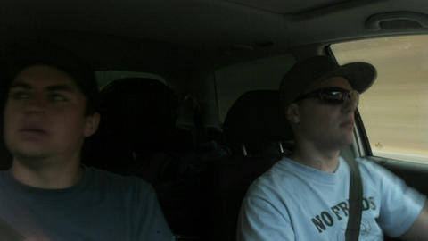 A passenger and a driver in a car smoke and eat Footage