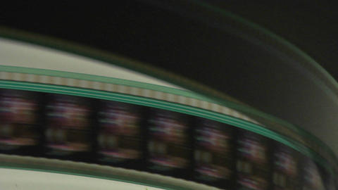 A film strip spools through a projector Stock Video Footage
