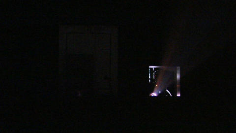 Light shines from a projector into a darkened theater Footage