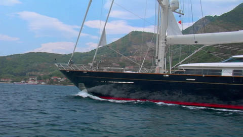 A medium shot of a sailing vessel moving along the coastline Stock Video Footage