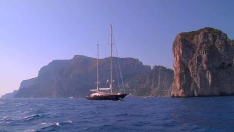 A medium shot of a sailing vessel moving along the Mediterranean coastline Footage