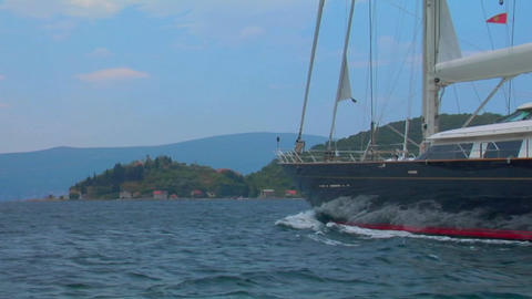 A medium shot of a sailing vessel moving along the Mediterranean coastline Footage