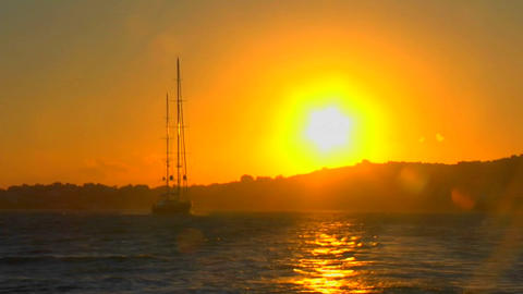 A sailboat cruises the high seas at sunset Stock Video Footage