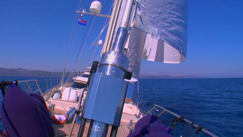 A pan across a sailboat in the Mediterranean as we tilt up to view the white sails Footage