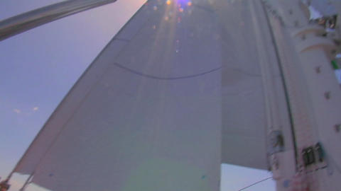 A sailboat's deck as it moves across the ocean and tilt up to sails Footage