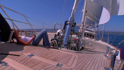 A sailboat's deck as it moves across the Mediterranean as we tilt up to the sail Footage