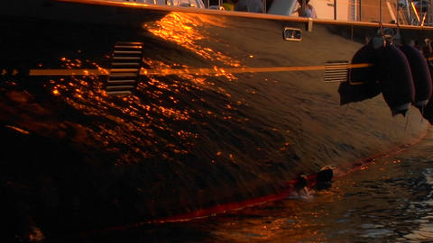 Sunset reflection on the hull of a sailboat docked in the harbor. Zoom out Footage