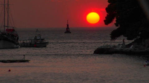 A Red setting Croatian sun sits just above the water at dusk Stock Video Footage