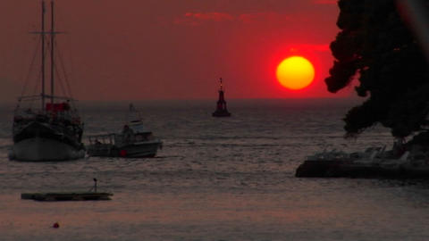 A Red setting Croatian sun sits just above the water at dusk Footage