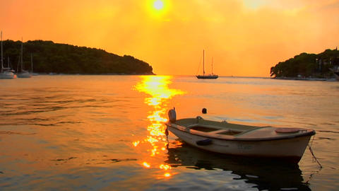A Small Boat Gently Floats As A Croatian Sunset Transpires stock footage