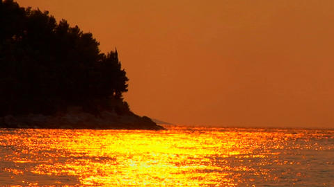 A Croatian sunset is reflected on the ocean, trees blow in the background Footage