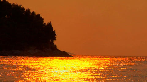 A Croatian sunset is reflected on the ocean, trees blow... Stock Video Footage