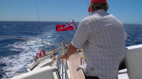 A view of the aft deck of a sailboat healing starboard, a man crosses the frame down to the aft deck Footage