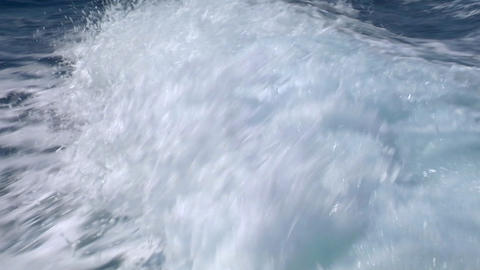 The wake of a ship is seen as it breaks repeatedly in... Stock Video Footage