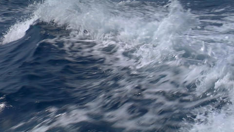 The wake of a ship is seen as it breaks repeatedly in slow motion Footage