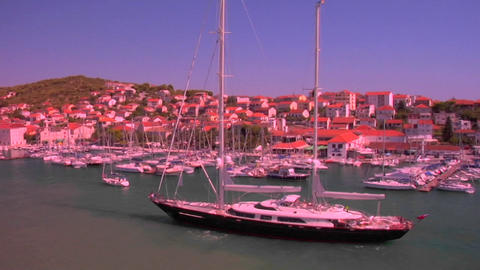 A large sailboat comes into port in the tiny town of Trojeir, Croatia Footage