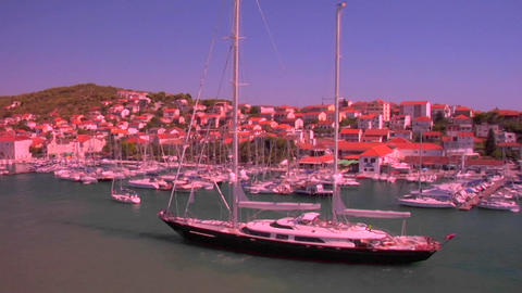 A large sailboat comes into port in the tiny town of... Stock Video Footage