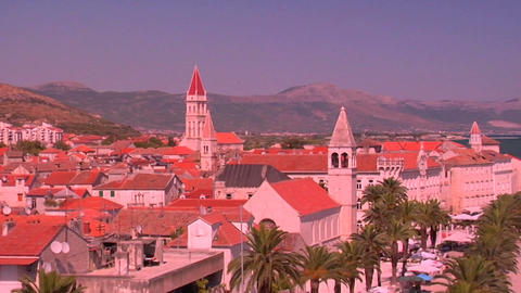 Aerial view of Trojir, Croatia's port and 1000 year old city. People walk along the port. Zoom out Footage