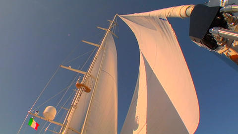 View of sails on sailboat from deck as the wind fills them Footage