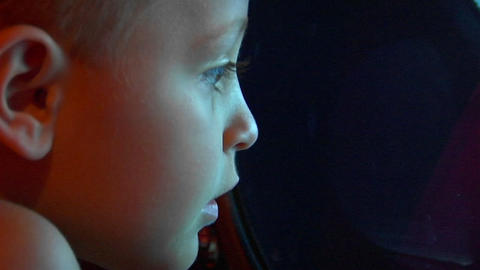 Young boy enjoys the view from the ship's port hole Stock Video Footage