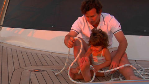 A father plays with his daughter on deck in the sunset Stock Video Footage