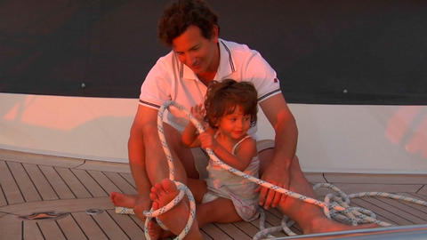 A father plays with his daughter on deck in the sunset Footage