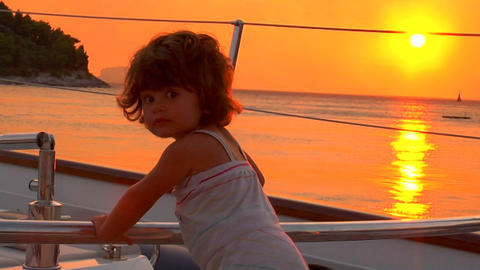 A 2 year old girl plays on the boat's deck at sunset Stock Video Footage