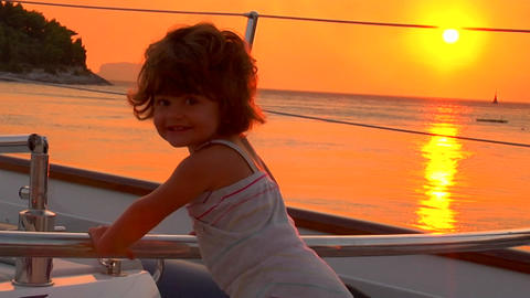 A 2 year old girl plays on the boat's deck at sunset Footage