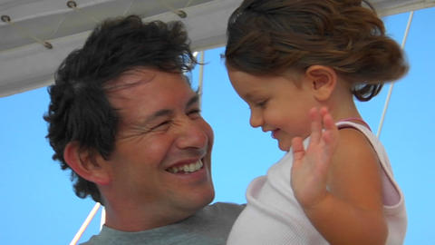 A father holds his daughter as they enjoy the strong... Stock Video Footage