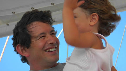 A father holds his daughter as they enjoy the strong winds during sailing Footage