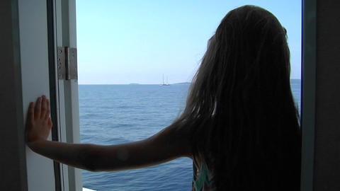 A girl stands in the doorway of a ship looking out on the water with the wind in her hair. Zoom in Footage